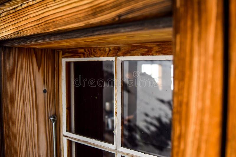 Opinião bonita do close-up de uma janela de madeira velha, resistida com um quadro de janela grande visto em uma cabine nos cumes imagens de stock