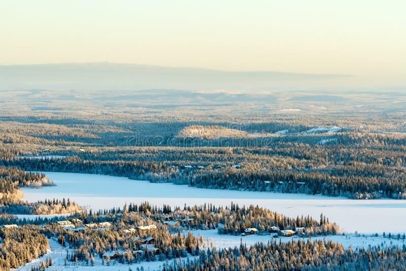 Opinião bonita do inverno do lago congelado e da floresta nevado em Finlandia, Ruka fotos de stock royalty free
