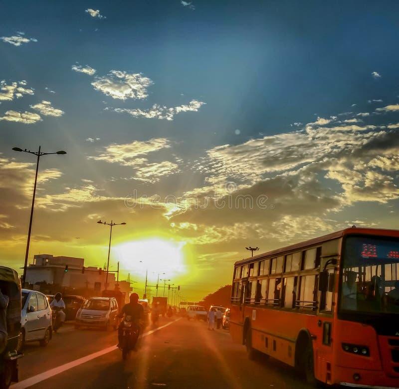 Opinião bonita do por do sol na estrada com tráfego ocupado fotografia de stock