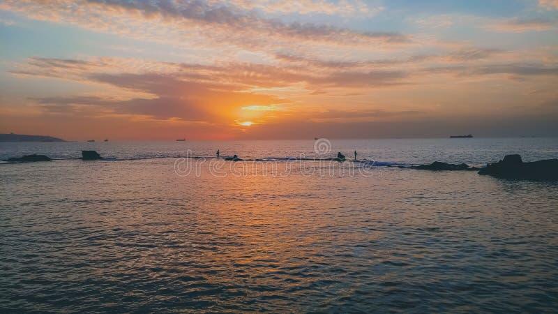 A opinião bonita do por do sol sobre o mar com navios e os pescadores mostram em silhueta imagem de stock royalty free
