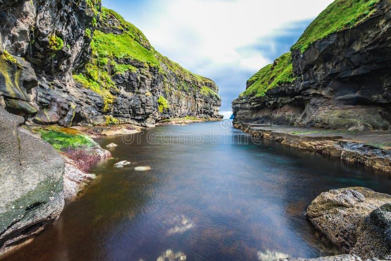 Opinião bonita a doca ou o porto com a rocha preta natural e a grama verde na vila de Gjogv com água clara profunda no norte azul imagens de stock royalty free