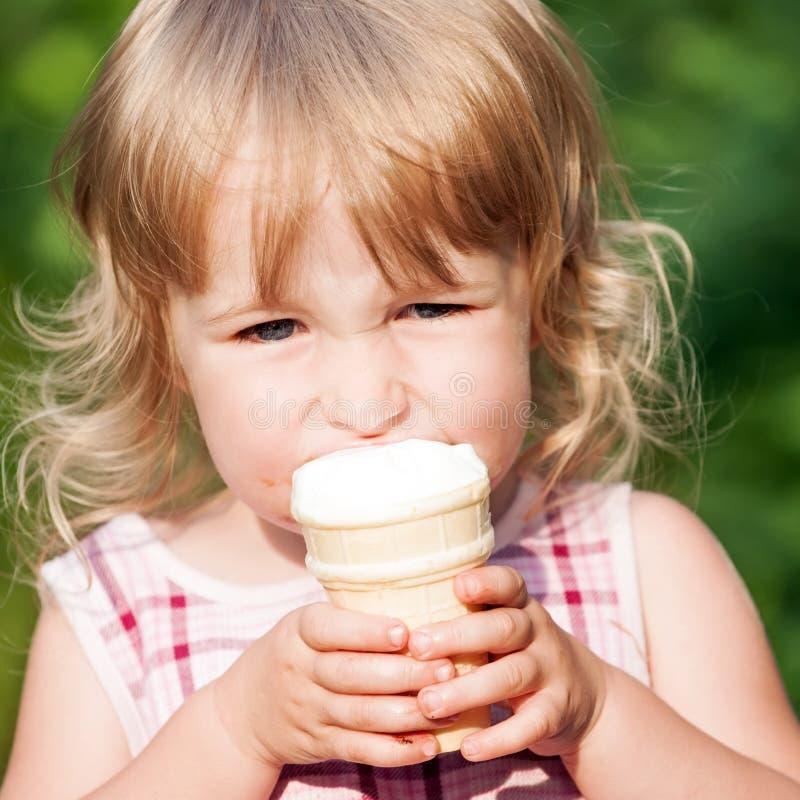 Opinião branca pequena da cara do close up do gelado comer da menina foto de stock royalty free