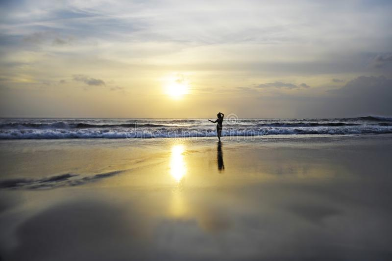 Opinião cênico da praia bonita surpreendente do por do sol com a silhueta da mulher que olha ao horizonte do oceano sob um céu al imagens de stock