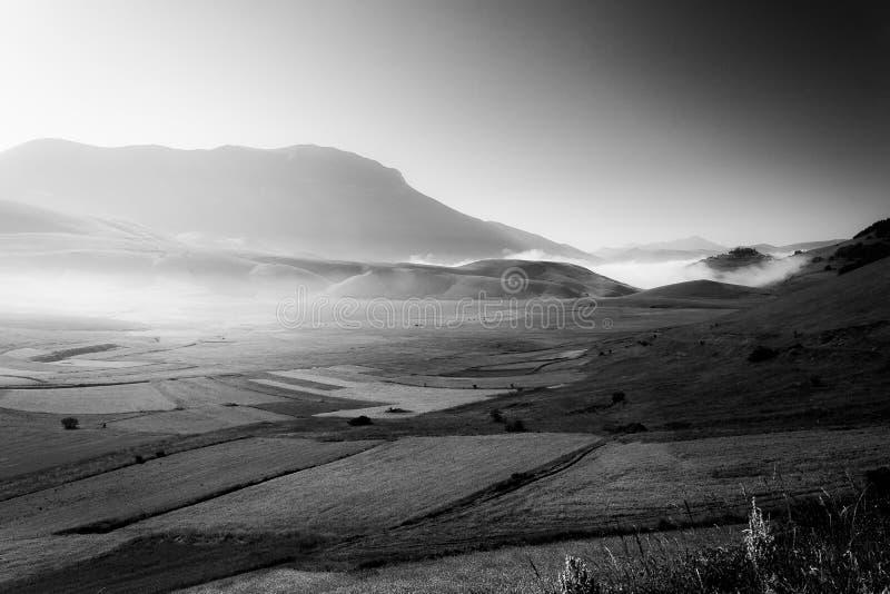 Opinião Castelluccio di Norcia Úmbria no alvorecer, com névoa, os prados grandes e o céu totalmente vazio imagens de stock