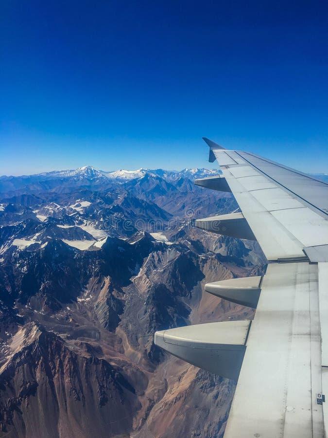 Opinião coberto de neve da janela do avião da montanha foto de stock
