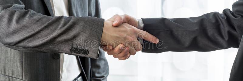 Opinião colhida larga dois homens de negócios que agitam as mãos imagens de stock royalty free
