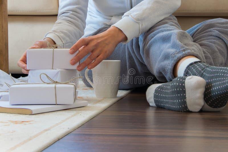 Opinião colhida a mulher com os pijamas que sentam-se no assoalho de madeira com bebida e as caixas de presente quentes imagens de stock royalty free