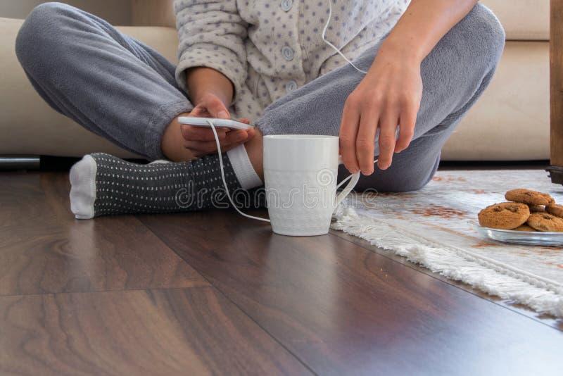 Opinião colhida a mulher com os pijamas que sentam-se no assoalho de madeira com bebida e as cookies quentes, usando um smartphon foto de stock royalty free