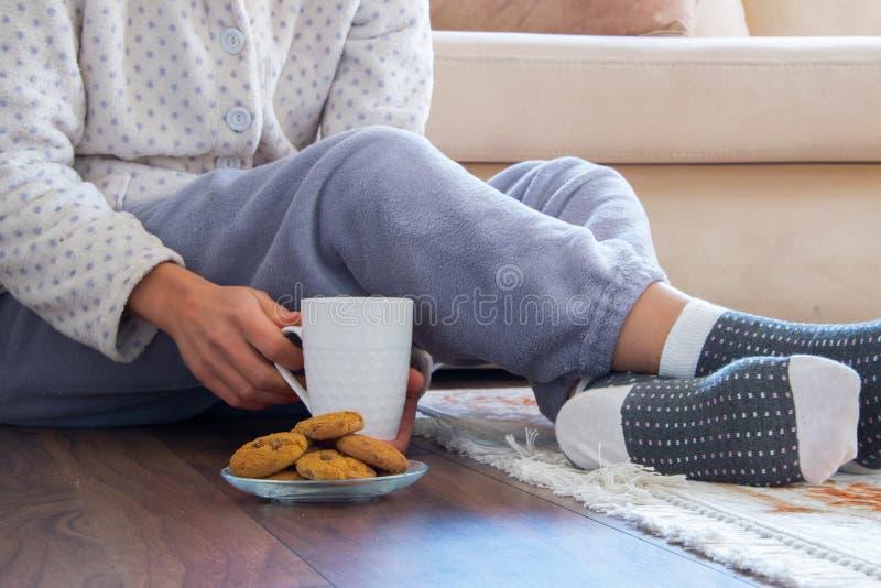 Opinião colhida a mulher com os pijamas que sentam-se no assoalho de madeira em casa com bebida e as cookies quentes imagens de stock royalty free