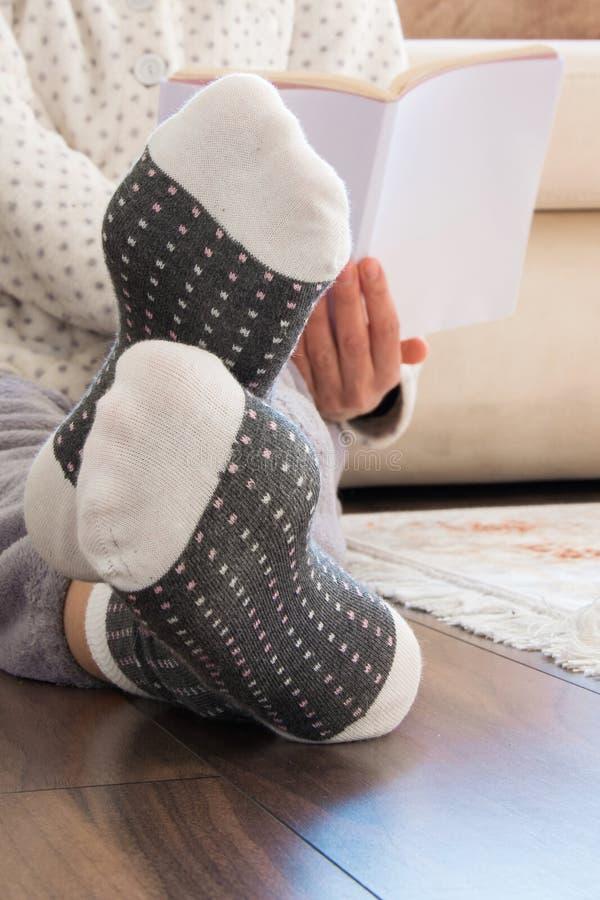 Opinião colhida a mulher com os pijamas que sentam-se no assoalho de madeira em casa com bebida e as cookies quentes, lendo um li imagem de stock