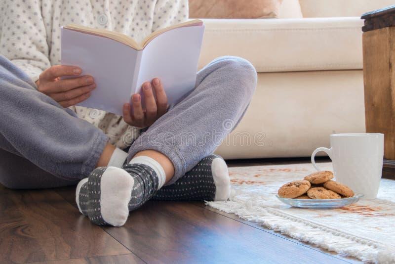 Opinião colhida a mulher com os pijamas que sentam-se no assoalho de madeira em casa com bebida e as cookies quentes, lendo um li foto de stock