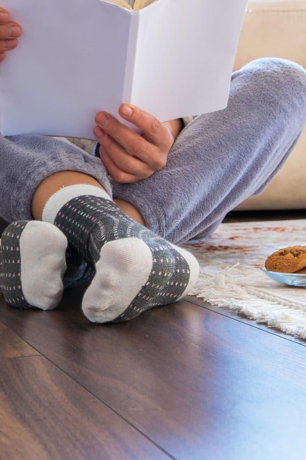 Opinião colhida a mulher com os pijamas que sentam-se no assoalho de madeira em casa e que leem um livro fotos de stock