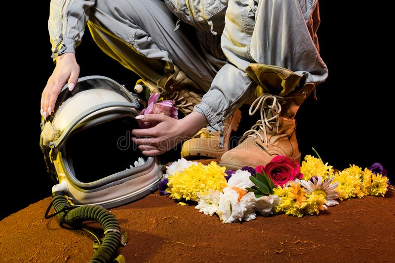 opinião colhida o astronauta no spacesuit com flores e assento do capacete foto de stock