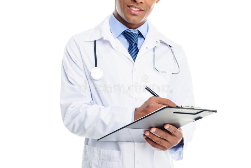 opinião colhida o doutor masculino afro-americano no revestimento branco com diagnóstico da escrita do estetoscópio na prancheta, imagens de stock royalty free
