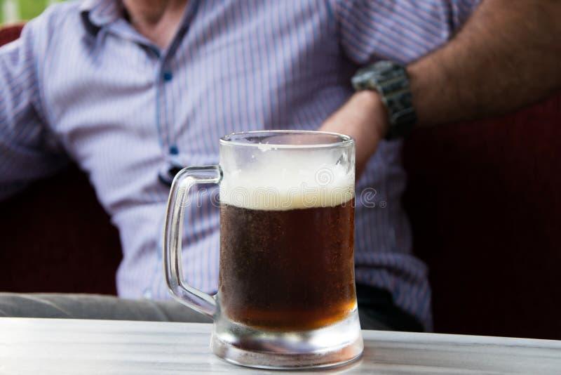 Opinião colhida o homem atrativo na camisa com a caneca de cerveja na tabela imagens de stock royalty free