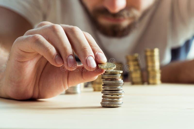 Opinião colhida o homem que empilha moedas na tabela imagens de stock