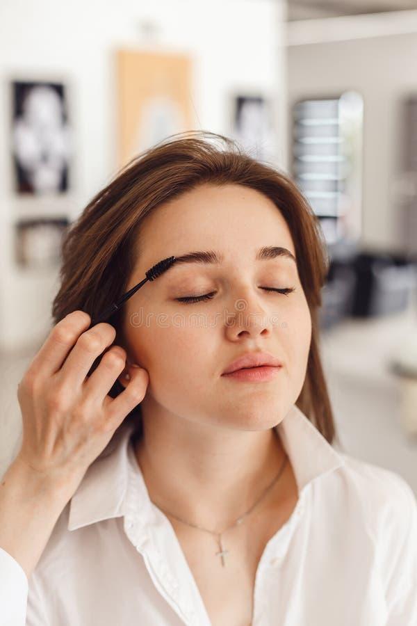 Opinião colhida uma jovem mulher que tem a cor da testa adicionada a suas sobrancelhas imagens de stock