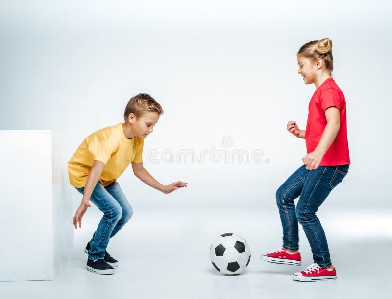 Opinião completa do comprimento irmãos felizes nos t-shirt coloridos que jogam com bola de futebol fotos de stock