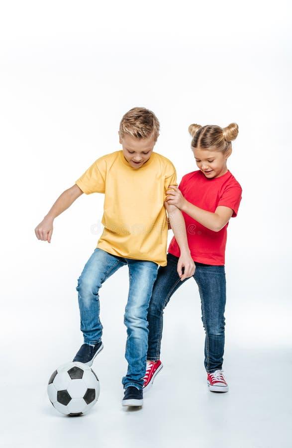 Opinião completa do comprimento irmãos felizes nos t-shirt coloridos que jogam com bola de futebol fotografia de stock royalty free