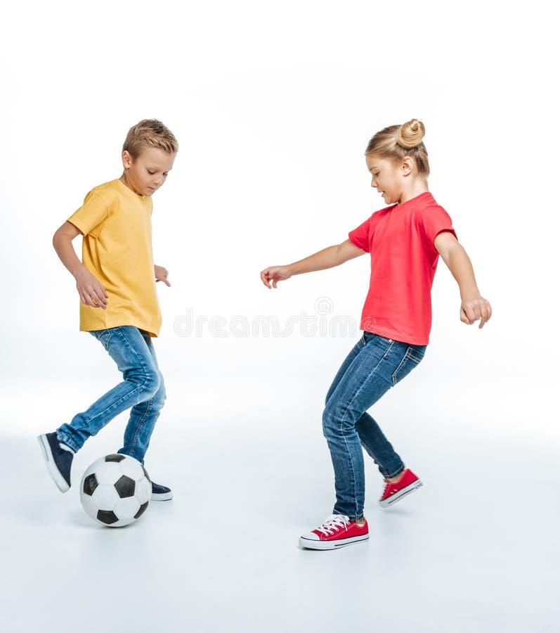 Opinião completa do comprimento irmãos felizes nos t-shirt coloridos que jogam com bola de futebol fotos de stock royalty free