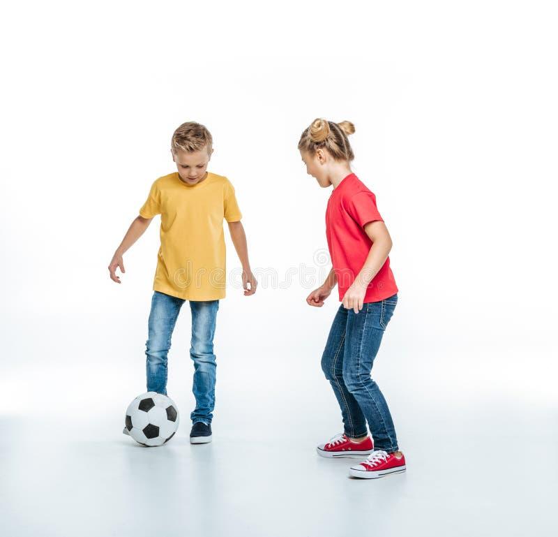 Opinião completa do comprimento irmãos felizes nos t-shirt coloridos que jogam com bola de futebol fotografia de stock