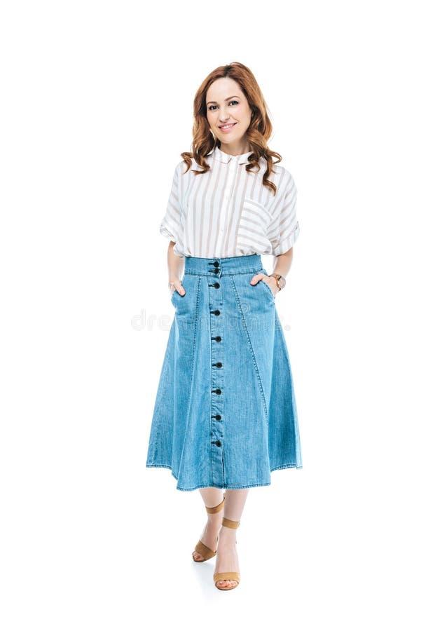 opinião completa do comprimento a mulher bonita que está com mãos em uns bolsos da saia da sarja de Nimes e que sorri na câmera fotos de stock royalty free