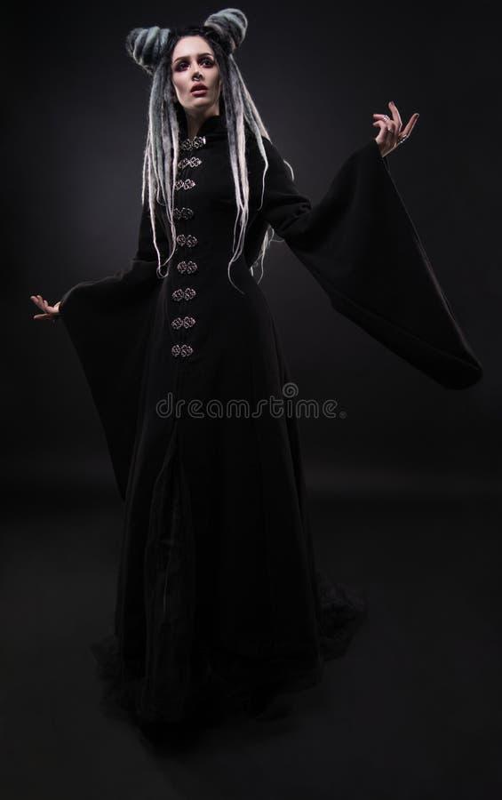 A opinião completa do comprimento a mulher com teme vestir o revestimento gótico preto fotografia de stock royalty free