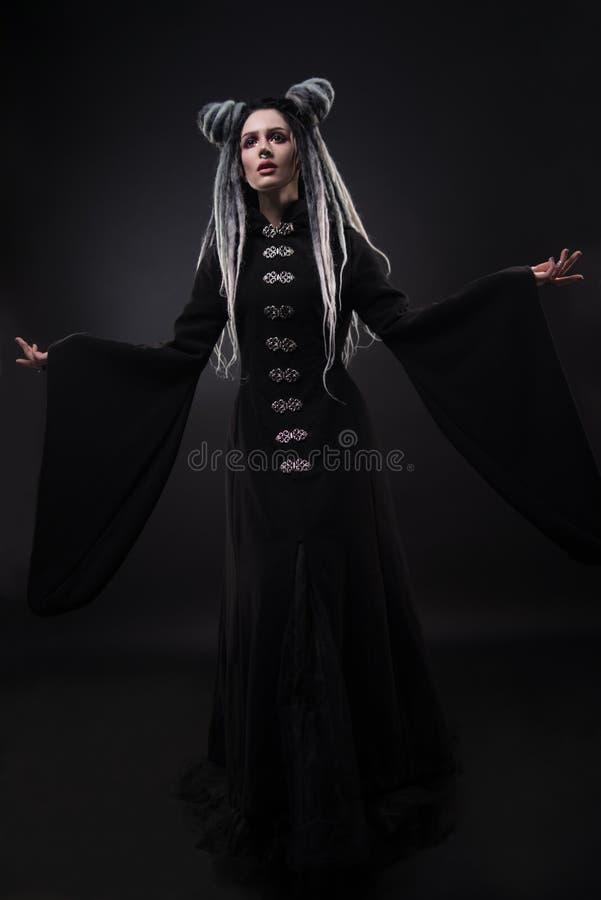 A opinião completa do comprimento a mulher com teme vestir o revestimento gótico preto imagem de stock royalty free