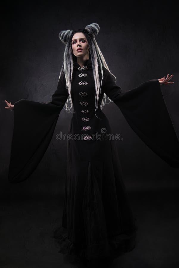 A opinião completa do comprimento a mulher com teme vestir o revestimento gótico preto foto de stock royalty free