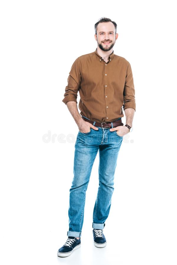opinião completa do comprimento o homem farpado considerável que está com mãos em uns bolsos e que sorri na câmera imagens de stock royalty free