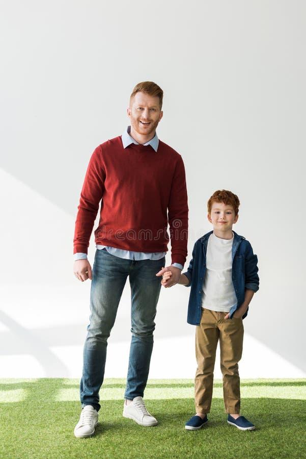 opinião completa do comprimento o pai feliz e o filho do ruivo que guardam as mãos e que sorriem na câmera foto de stock royalty free