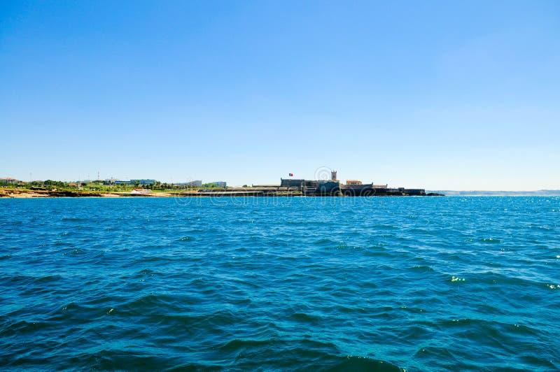 Opinião da água - fortaleza na praia de Carcavelos, subúrbios de Lisboa, bandeira portuguesa foto de stock