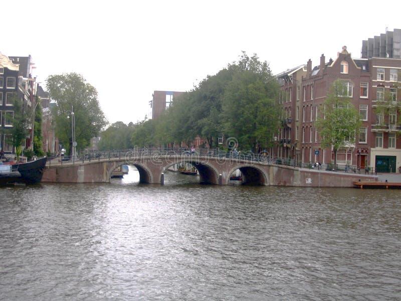 Opinião da arquitetura da cidade com canal, pontes, ruas e as casas holandesas tradicionais em Amsterdão, Países Baixos imagem de stock