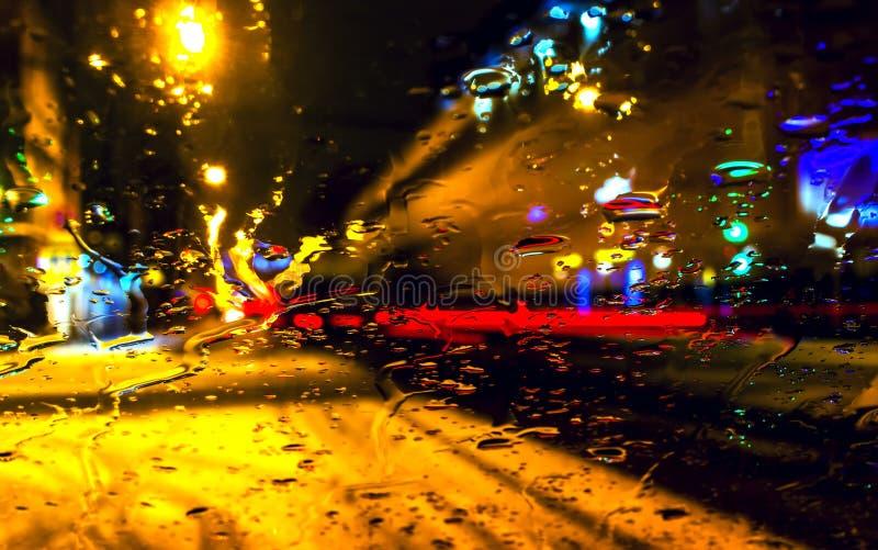Opinião da cidade com obscuro com chuva pesada na janela de carro O fundo de Blured com chuvas deixa cair no vidro e na loja-jane imagens de stock