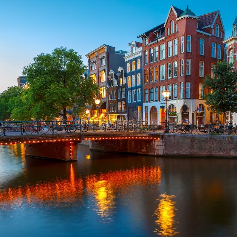 Opinião da cidade da noite do canal de Amsterdão com hous holandês fotografia de stock