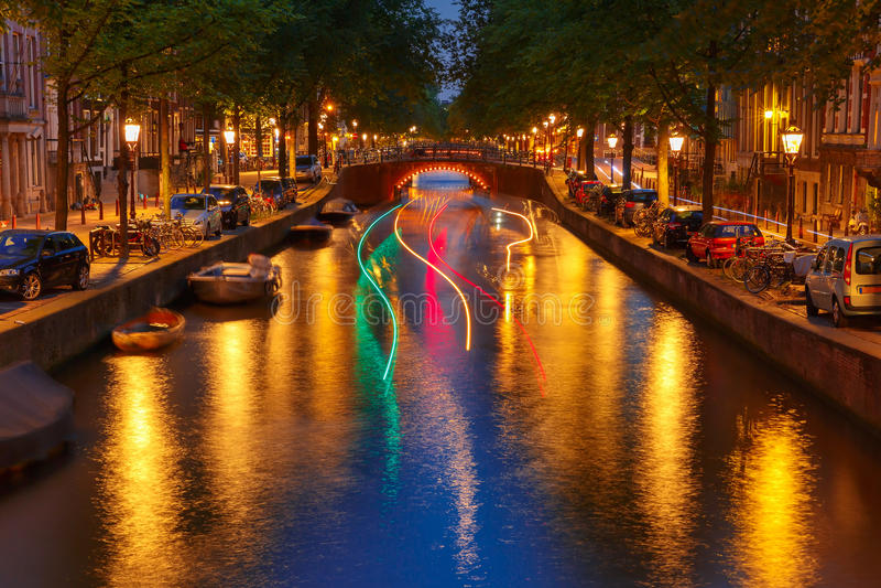 Opinião da cidade da noite do canal de Amsterdão e da trilha luminosa do b fotos de stock