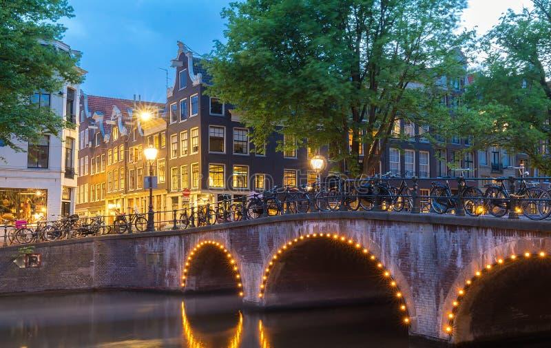 Opinião da cidade da noite do canal de Amsterdão, casas holandesas típicas, Holanda, Países Baixos fotos de stock royalty free