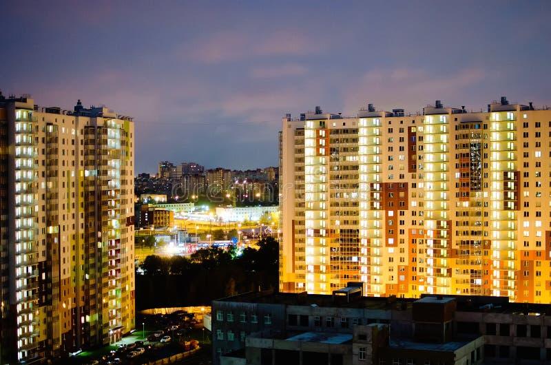 Opinião da cidade da noite prédios de apartamentos do Multi-andar com janelas luminosas contra um céu escuro imagens de stock