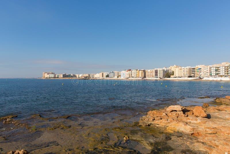 Opinião da Espanha de Torrevieja dos loucos do Los através da baía a encalhar e dos prédios de apartamentos do feriado fotos de stock