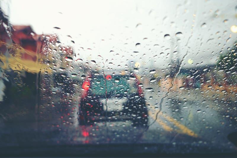 A opinião da estrada através da janela de carro com chuva deixa cair fotos de stock royalty free
