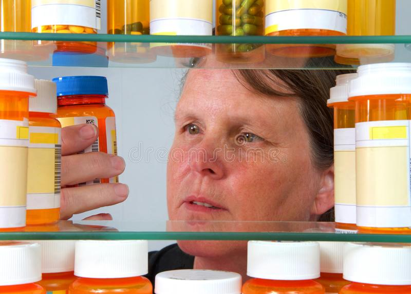 Opinião da etiqueta da prescrição da leitura da mulher através do armário do MED fotografia de stock royalty free
