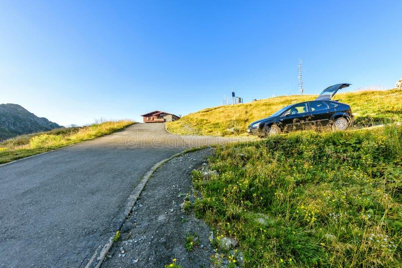 Opinião da luz do dia à estrada à casa de campo com o carro estacionado no lado fotografia de stock royalty free
