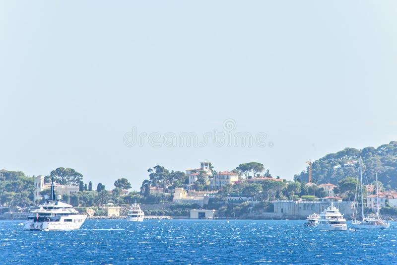 Opinião da luz do dia aos iate brancos e aos barcos que cruzam na água fotografia de stock royalty free