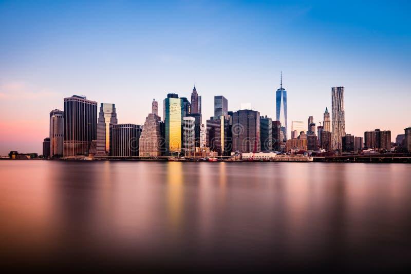 A opinião da manhã de uma mais baixa silhueta de Manhattan que reflexing na claro molha de East River fotografia de stock