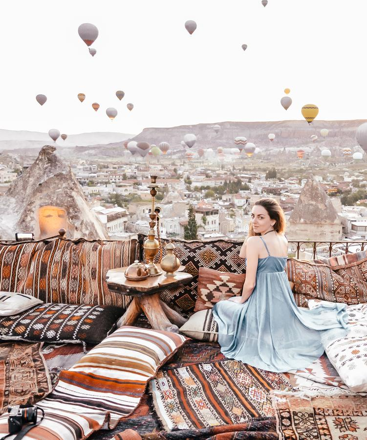 Opinião da manhã em Cappadocia Opinião do terraço na mulher de Goreme com os balões e os tapetes de ar quente imagens de stock