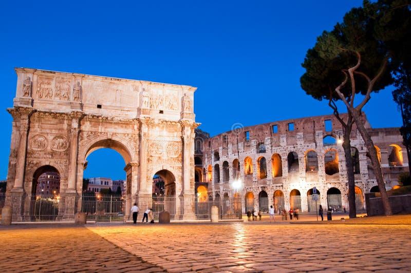 Opinião da noite Arco di Costantino e colosseo em Roma foto de stock