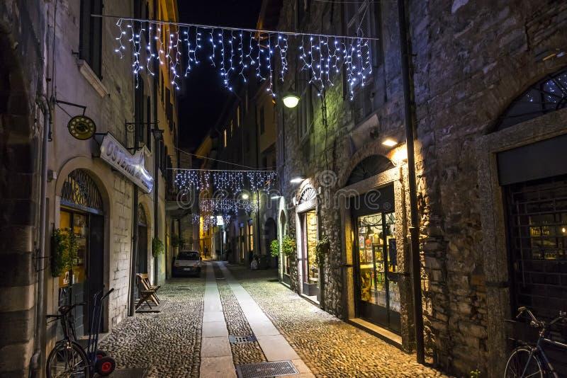 Opinião da noite através da rua de Vitani na cidade velha de Como, Itália imagem de stock