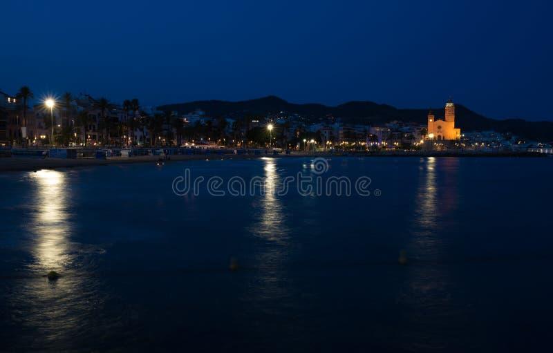 Opinião da noite da costa na cidade de Sitges perto de Barcelona em Catalonia, Espanha com a igreja de Parroquia de Sant Bartomeu fotografia de stock royalty free