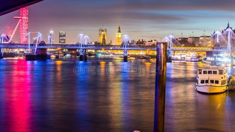 Opinião da noite da ponte de Hungerford e de pontes douradas Londo do jubileu imagens de stock
