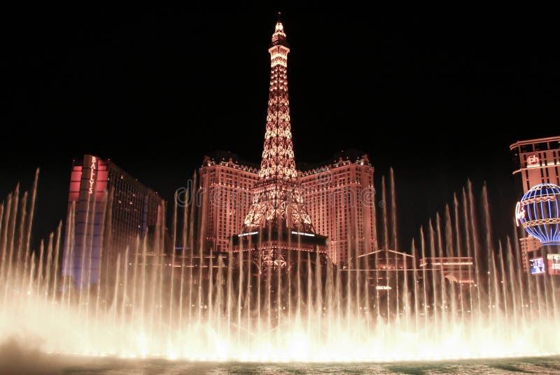 : Opinião da noite das fontes da dança de Bellagio e da réplica da torre Eiffel fotografia de stock royalty free